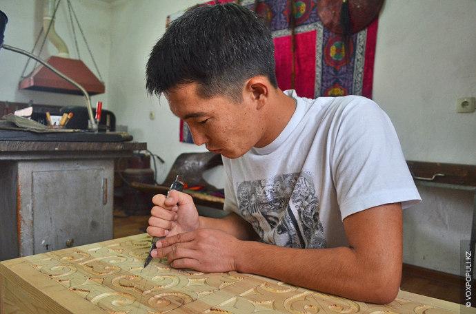 Мади предпочитает работать с деревом. На снимке он вырезает узор на деревянной доске, которой предстоит...