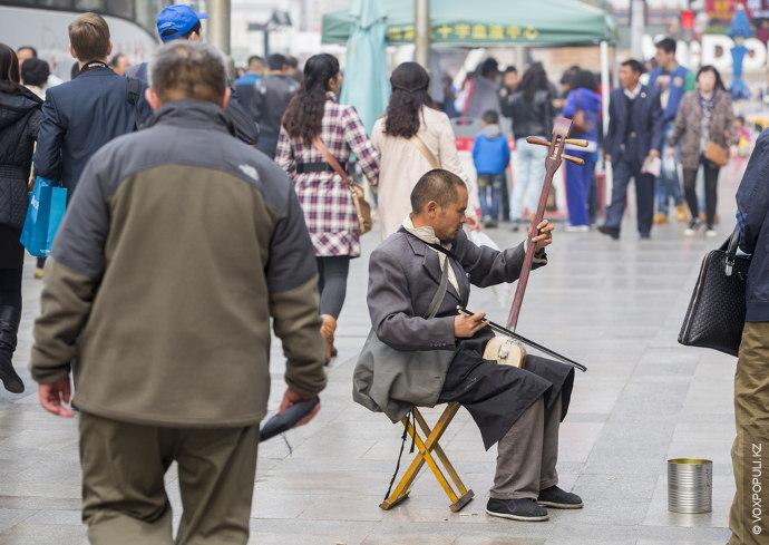 Благополучие и бедность на одной улице. Попрошайки в Пекине зарабатывают на хлеб собственным талантом.