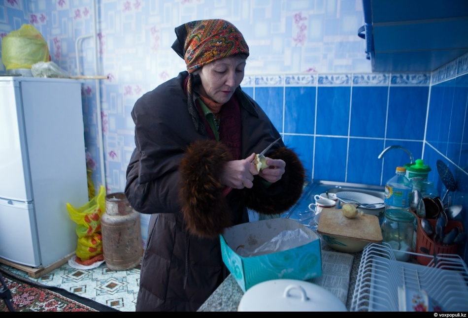 Former dentist with 25 years of working experience Aliya Kaldybayeva is cooking a meal wearing...